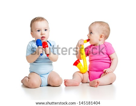 Babies girl and boy play musical toys. Isolated on white background