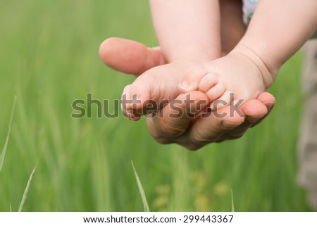 Babies legs in the father's hand. White building construction on the background.