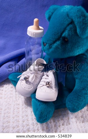 Babies shoes, Teddy Bear and Bottle - stock photo