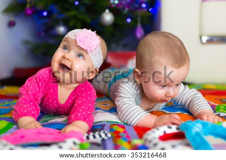 Babies with presents under Christmas tree - stock photo