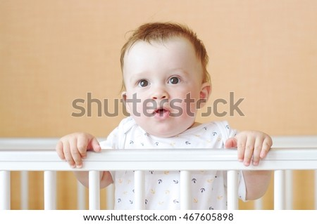 baby age of 9 months in white bed
