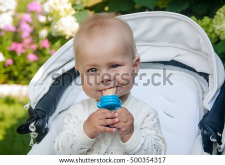 Baby age of 7 months sitting in a stroller and eats with nibbler (food feeder)