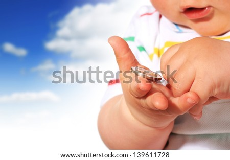 Baby and coin over sky background. - stock photo