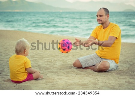Baby and father on the tropical beach playing toy ball - stock photo