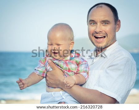 Baby and father outdoor portrait - stock photo