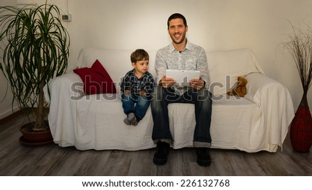 Baby and father playing with tablet on a white sofa smiling with red pillow and little bear - stock photo