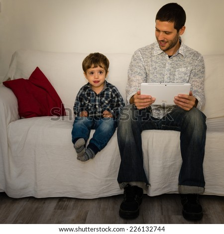 Baby and father playing with tablet on a white sofa while baby is making a bigmouth - stock photo