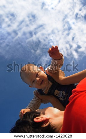 Baby and his mother are having outdoor fun together. The mother lifts him higher and higher and they are smiling a lot.