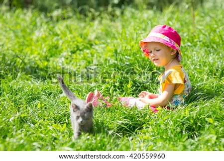 Baby and kitten playing in the garden - stock photo