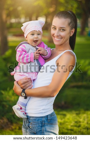 baby and mom are playing  in the park
