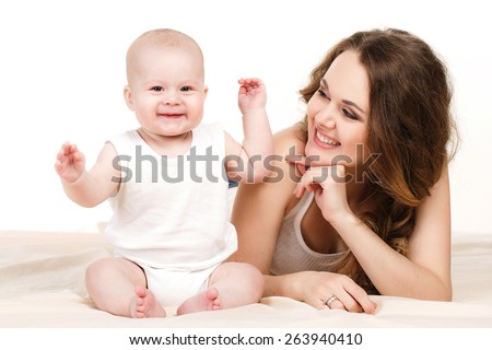 Baby and mother, childhood, motherhood, happy family. Young mother with baby boy. Sitting on white cloth and having fun - stock photo