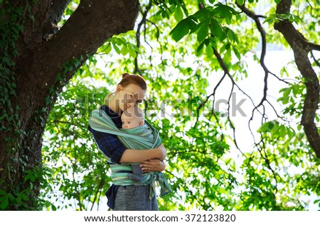 Baby and mother on nature in the park - stock photo