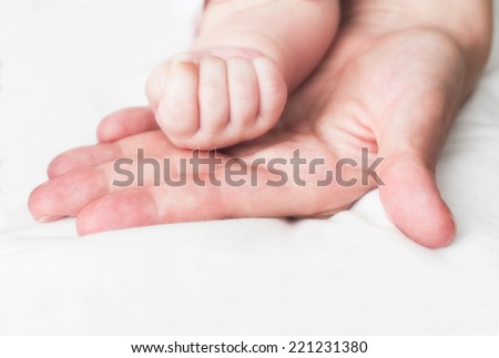 Baby and mother's hands - stock photo