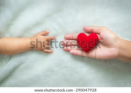baby and mothers hands made symbol of love. - stock photo