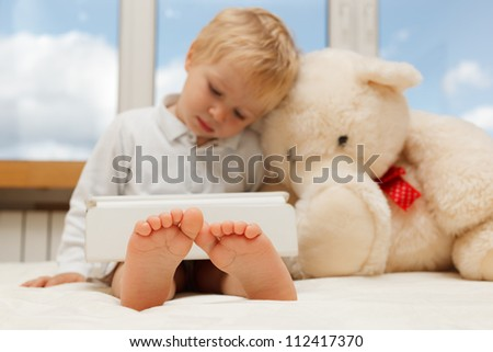 baby and teddy bear with touch pad at home