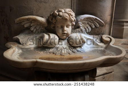 Baby angel over holy water stoup in church. Aged photo.  - stock photo