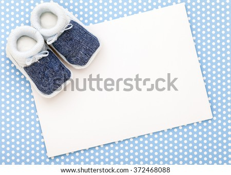 Baby announcement card with blue shoes on polka dot background.