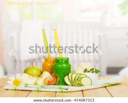 Baby apple puree, vegetable, dummy and cloth on a background of the kitchen.