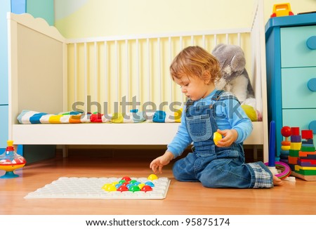 Baby assemble a mosaic in the kids  room - stock photo