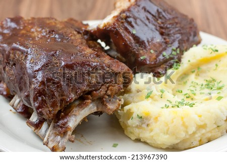 Baby back ribs and cheddar garlic mashed potatoes with green chives on top. - stock photo
