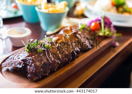 Baby back ribs with sauce served on a wooden plate with side dishes and sauces