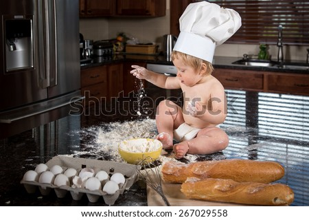 Baby baker in hat playing with flour - stock photo