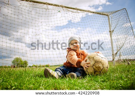 Baby Ball played football at the gate. - stock photo