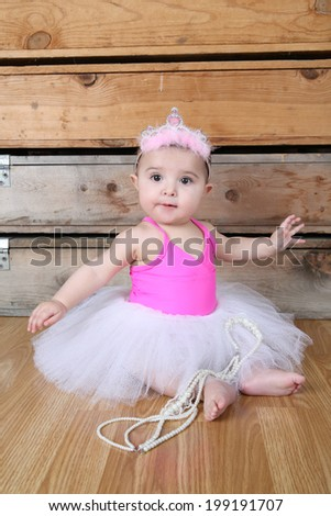 Baby ballerina wearing a white tutu and pink bodysuit