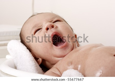 Baby bathing and yawning - stock photo