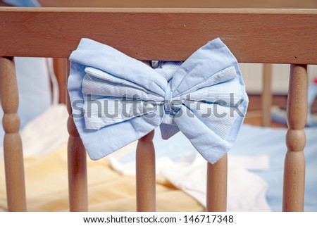 Baby bed with blue bow / baby bed - stock photo