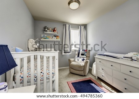 Baby bedroom interior, boy's room.  Gray walls and white wooden furniture: chest of drawers, crib.