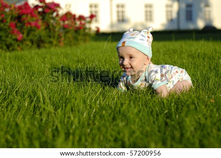 baby being a novice on the grass in a garden - stock photo