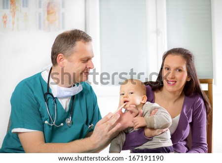 baby being checked by a doctor - stock photo