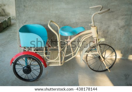 Baby Bicycle with 3 wheel. Vitnage metal Tri-cycle toy. Mini Bicycle toy for baby. Baby riding cart with pedals.  - stock photo