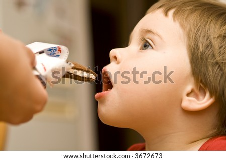Baby biting a candy bar - stock photo