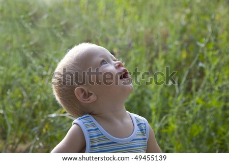 Baby blond boy summer outdoors at the grass