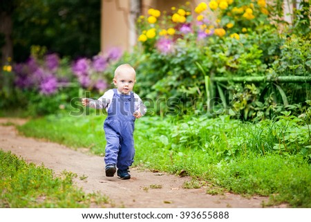 baby (blond girl) walks in the yard in the summer - stock photo