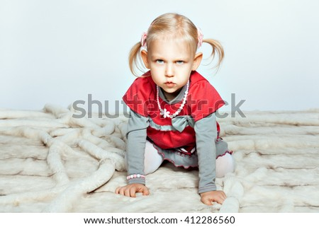 Baby blonde girl is on all fours and grimaces - stock photo