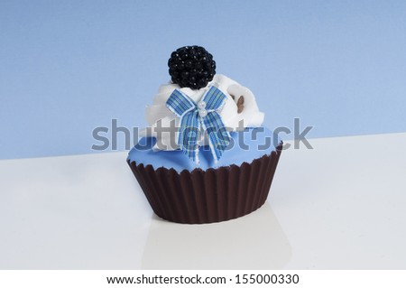Baby blue cupcake with a bow and fruit on top - stock photo