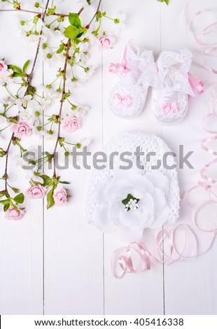 baby booties, cap and flowers on a white background