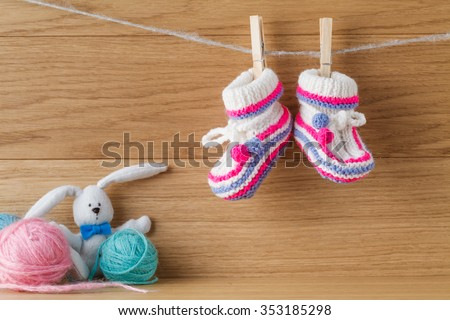 Baby booties hanging on a rope with paper note for invitation - stock photo