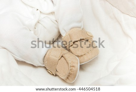 baby booties on the feet of the baby - stock photo
