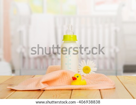 Baby bottle of milk, a towel and a rubber duck on the background of the kitchen. - stock photo