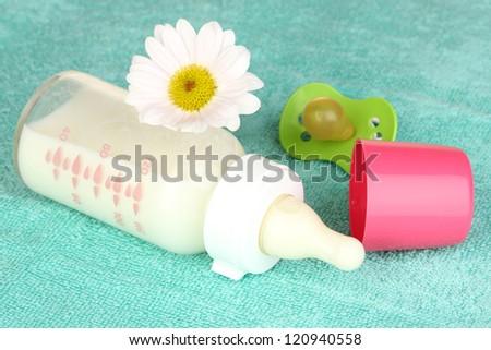 Baby bottle of milk on blue towel - stock photo