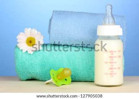 Baby bottle of milk with pacifier and towels on blue background - stock photo