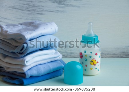 Baby bottle with  breast milk accessories on table on grey wooden background. Mother care breast milk  healthy food baby. children's room, the pile of blue clothes for newborn boy - stock photo
