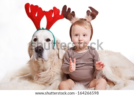 Baby boy and dog wearing reindeer antlers in front of white background - stock photo