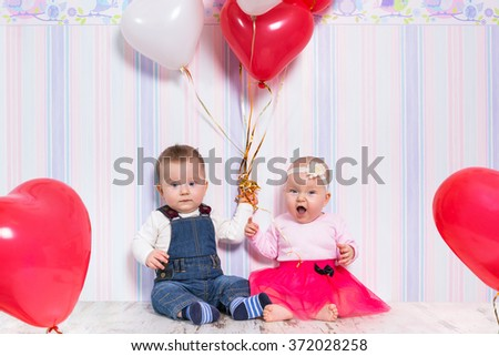 Baby boy and girl playing with heart balloons for valentines day. - stock photo