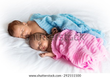 Baby boy and girl twins lying down in bed - stock photo