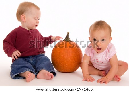 Baby boy and girl with a pumpkin. Girl in pink has a funny surprised, shocked expression. - stock photo